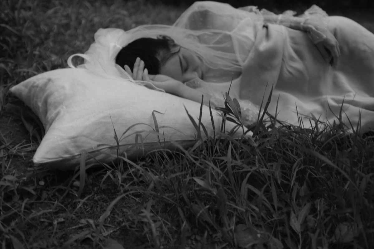 monochrome photo of woman sleeping on ground
